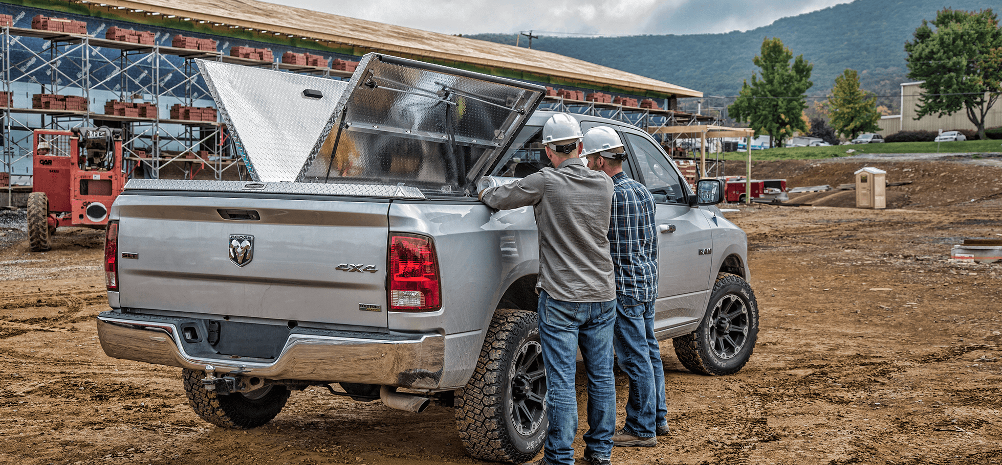 open 180 aluminum tonneau cover at construction site with two guys standing at truck