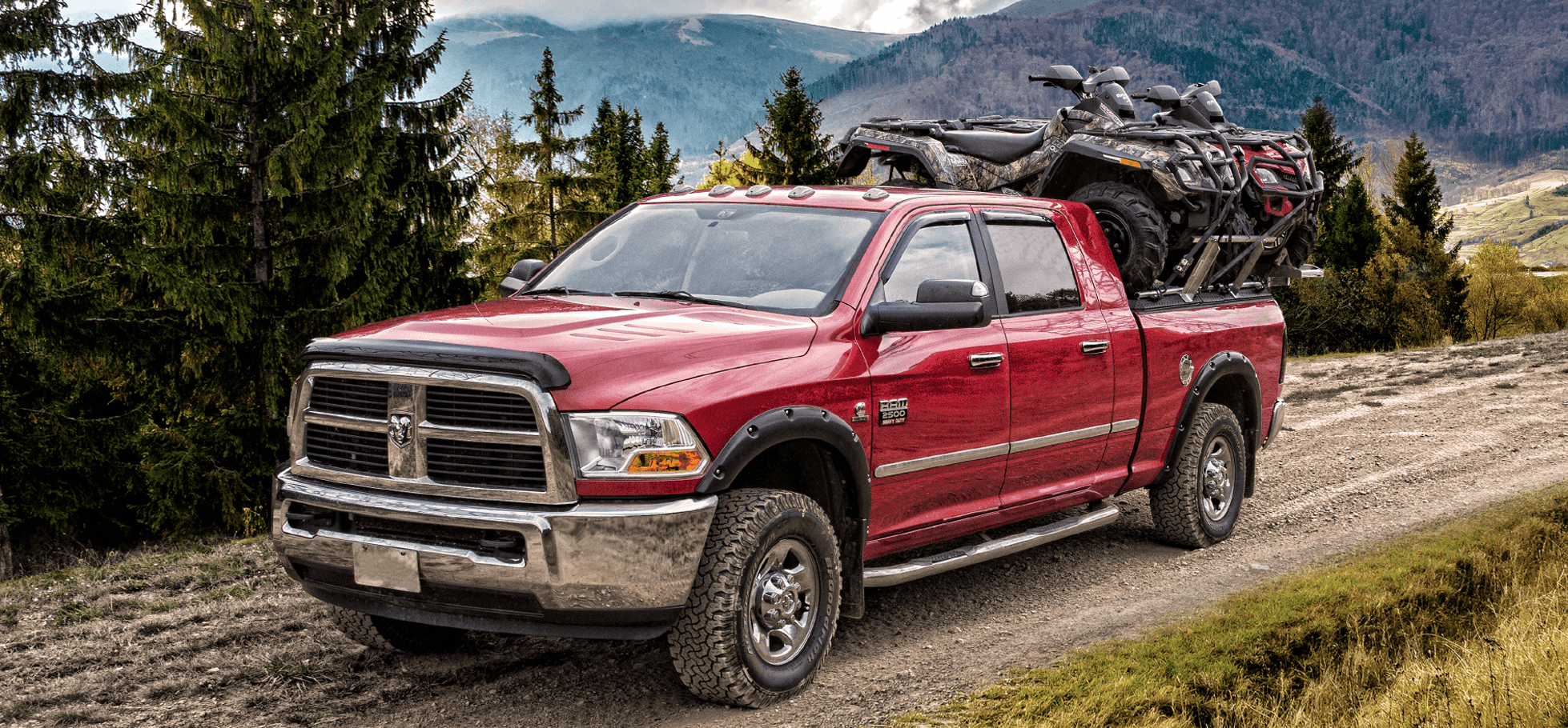 two atvs on atv truck rack on ram truck on top of mountain