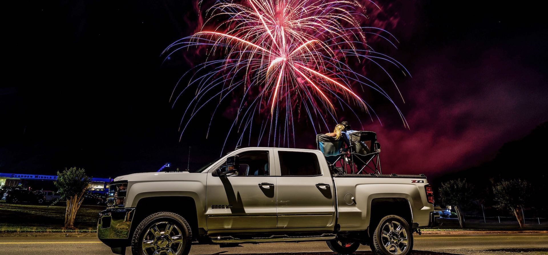Fireworks above couple on top of a DiamondBack HD diamond plate bed cover on Chevy Silverado