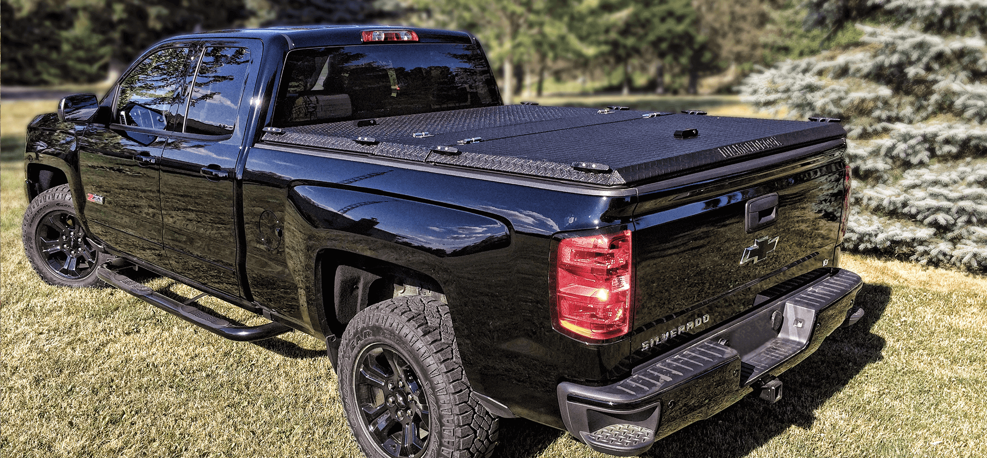 HD diamond plate bed cover on chevy silverado in trees