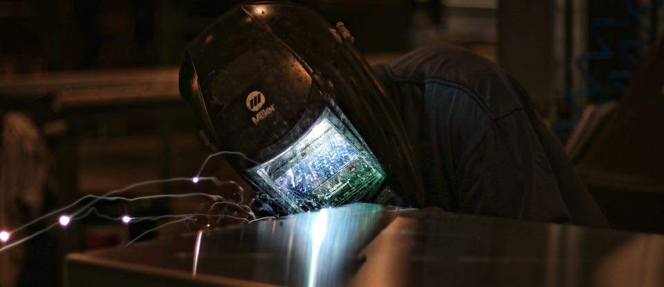A DiamondBack employee welds a Cross Bin 13