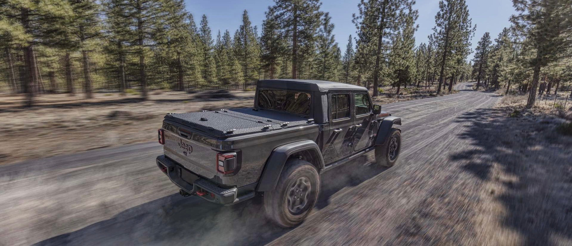 Jeep Gladiator with DiamondBack HD truck cover speeding down a gravel trail
