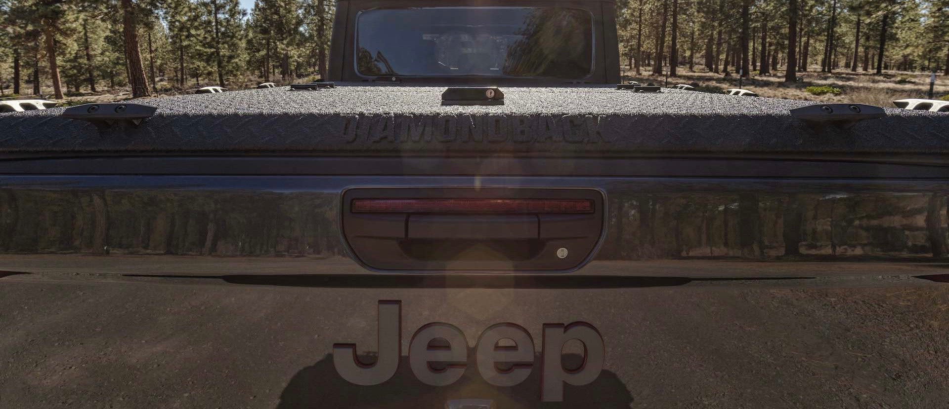 A man closes the door of his Jeep Gladiator that sports a DiamondBack HD truck cover