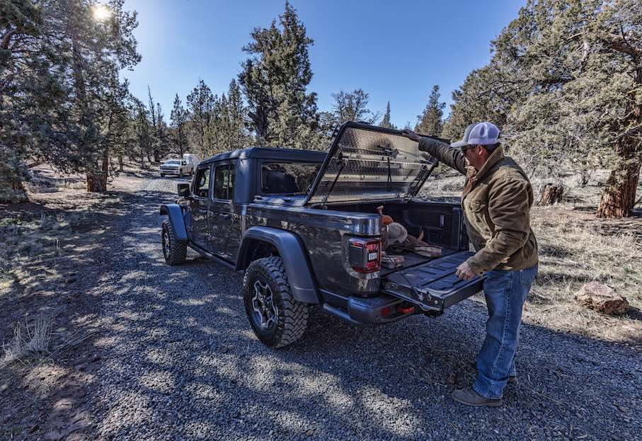 A man closes his DiamondBack HD truck cover to secure the saddle in the cargo bed of his Jeep Gladiator