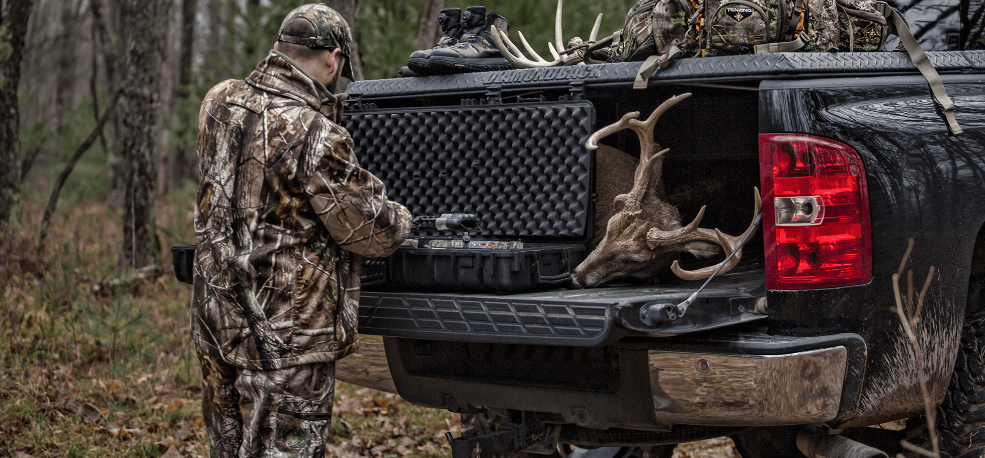 hunter at rear of 270 hard truck bed cover on chevy silverado with deer