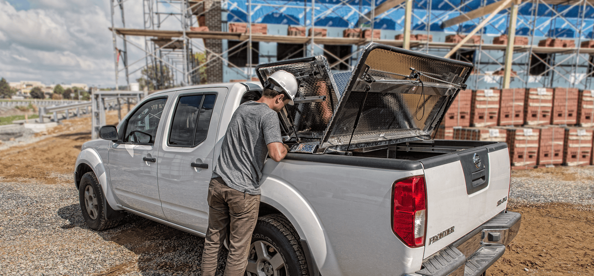 worker at side of nissan frontier with 270 hard truck bed cover