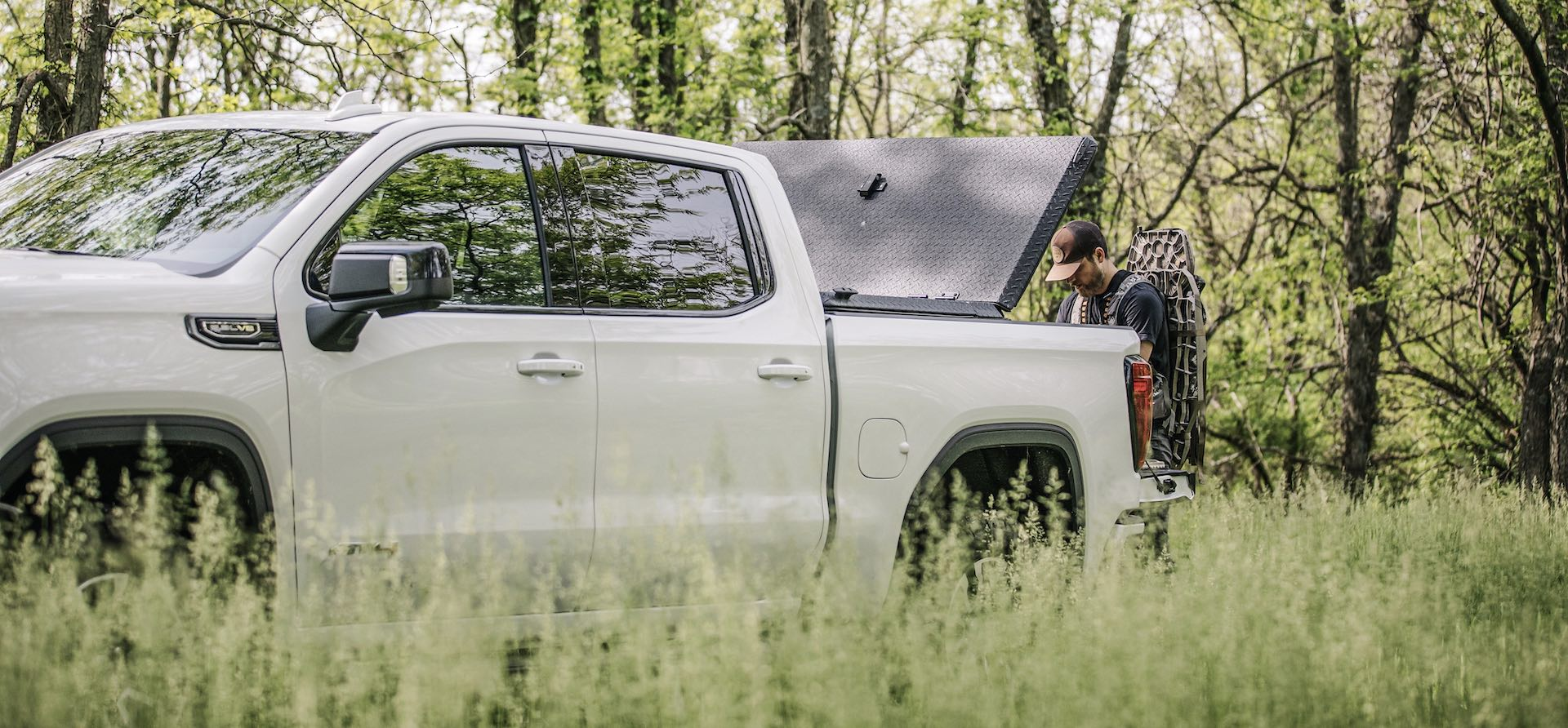 Man with tree stand, DiamondBack SE metal bed cover, and GMC Sierra