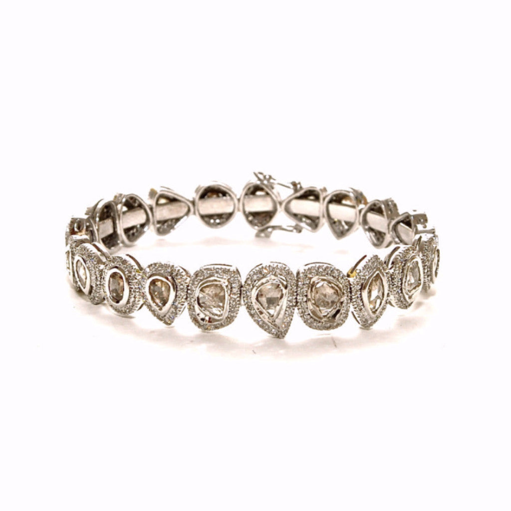 Image of a sterling silver bangle featuring roce-cut and pavé diamonds wrapped all the way around.