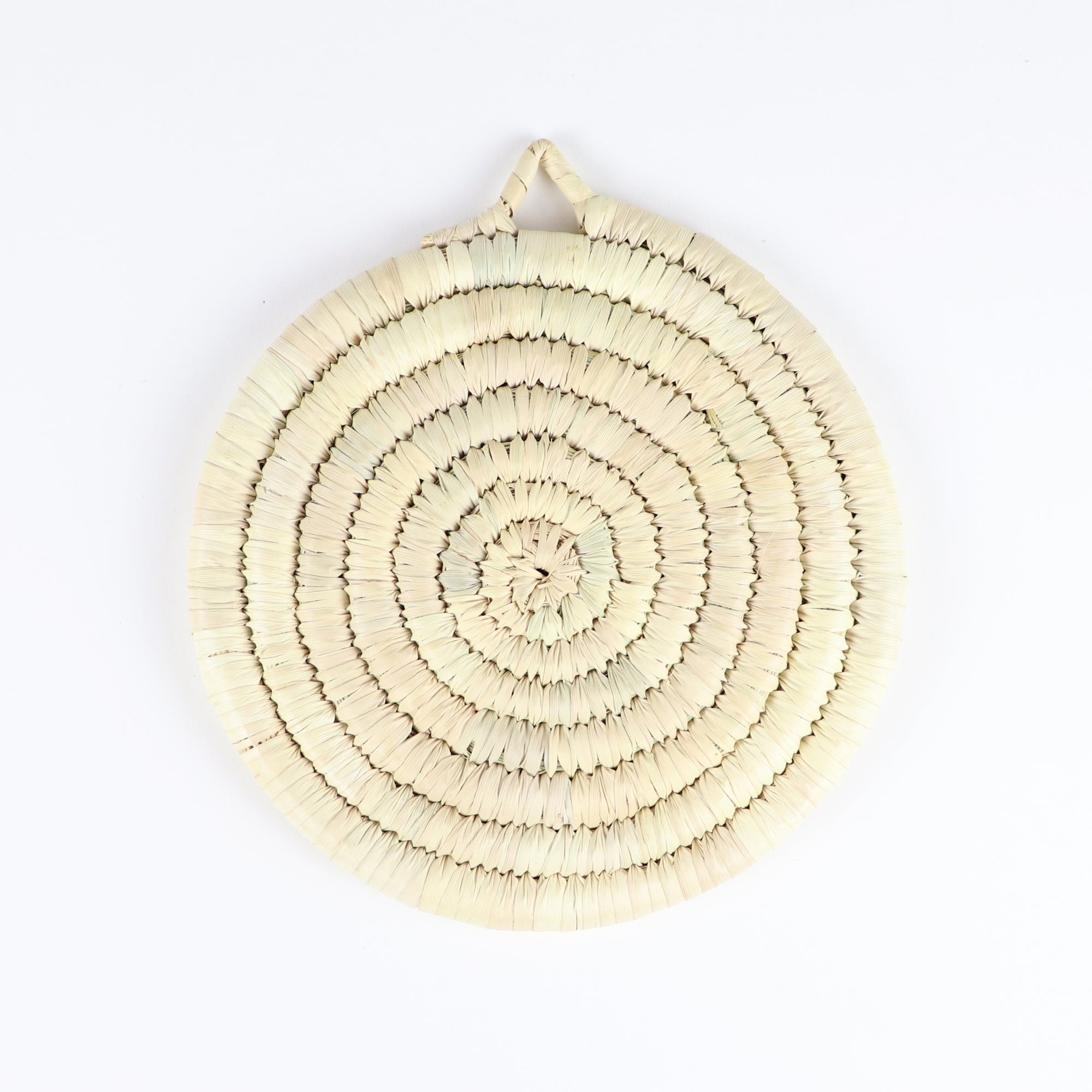 Straw trivet on top of a white table linen