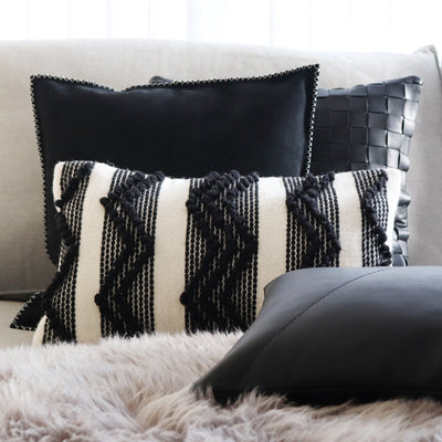 Pillows set up on top of a grey couch, mix of leather and wool