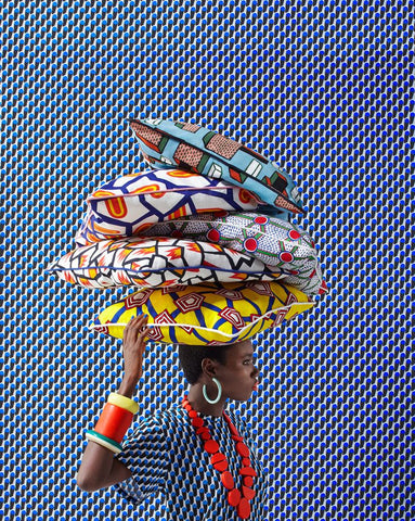 Woman carrying decorative pillows made with African print fabrics - Photo Source: Pinterest