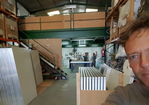 A member of the Glice Production Team taking a selfie in their warehouse with his teammates as background.