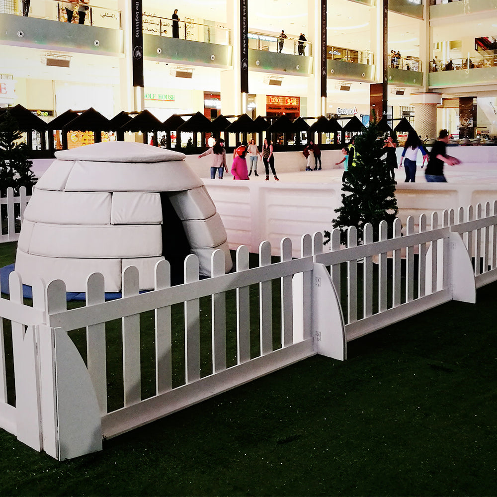 image of a desertsnow.ae supplied soft play igloo in a children's play area cordened off by white picket fences and set-up indoors for a winter-themed event and available for sale or hire across the middle east in salalah, jeddah, sharjah, abu dhabi, doha, muscat, riyadh, dubai, kuwait city, al ain, damman, jeddah and manama
