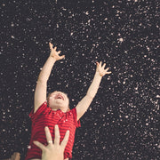 A child trying to touch the falling snow at Horizon English School Dubai