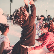Child playing with Display Snow inside Desert Snow's Snow Fight Zone at La Mer Dubai