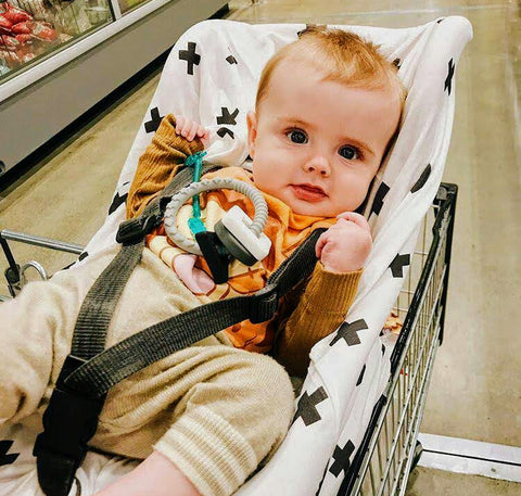 baby sitting on shopping trolley baby seat using a 5in1 multi cover