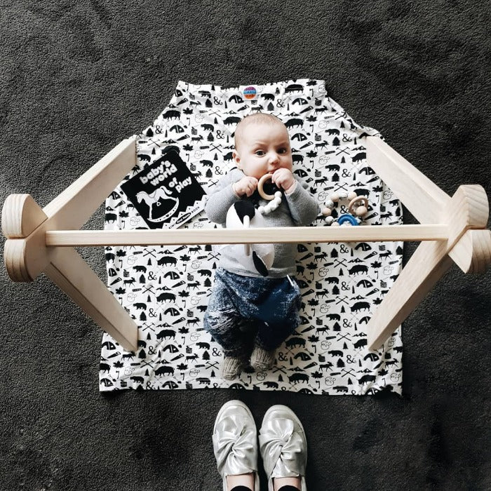 baby laying on the floor over a capsule cover with different forest designs in black on white fabric cotton capsule cover, playmat