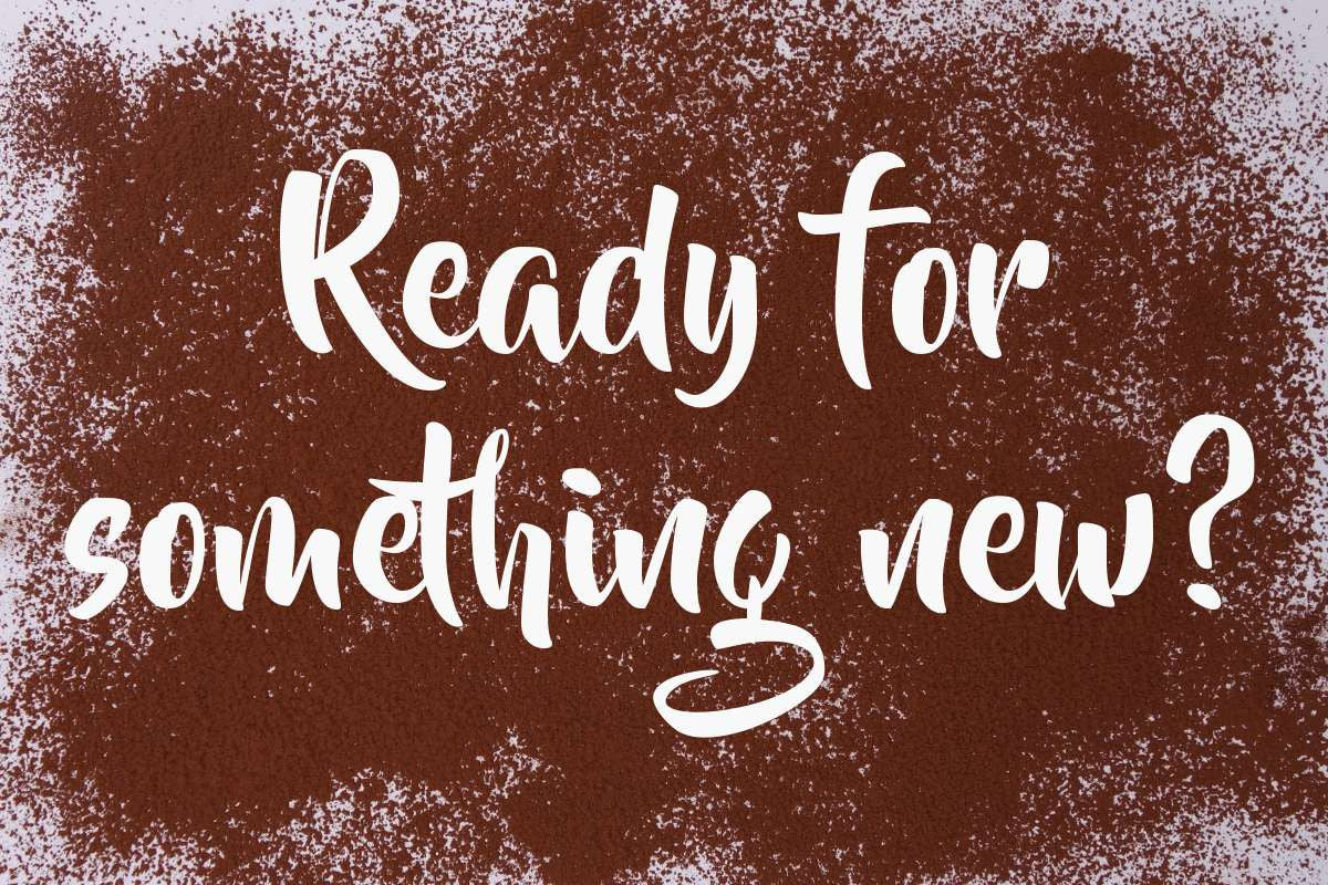 "The text ""Ready for something new?"" sprinkled around with cocoa powder"