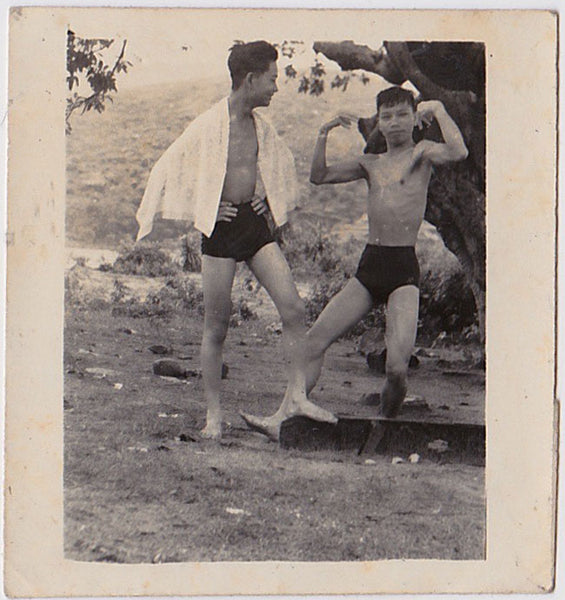 Undated vintage photo of two Asian men in swimsuits, one of whom watches the other flexing his biceps.