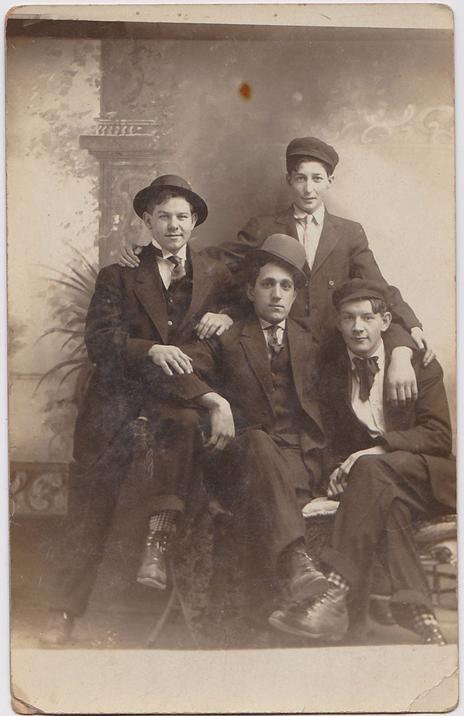 "Four affectionate men in a studio setting. Great socks!  Vintage sepia Real Photo Postcard, gloss finish. 3 1/2"" x 5  1/2,"" undated c. 1912."