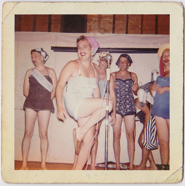 "Bunch of guys who seem to be enjoying their girlie moment on stage. The contestant on the left wears a ""Miss Steak"" ribbon."
