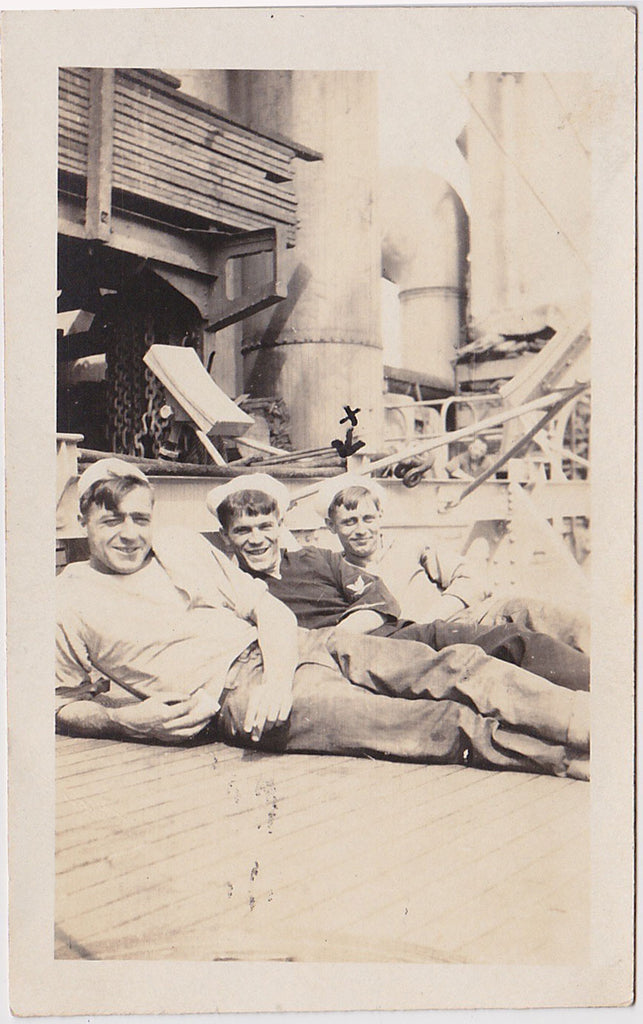 3 smiling sailors recline on deck
