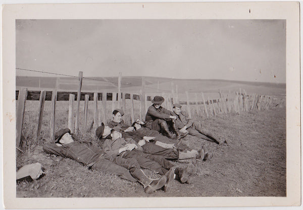happy soldiers recline along fence vintage snapshot 1930s
