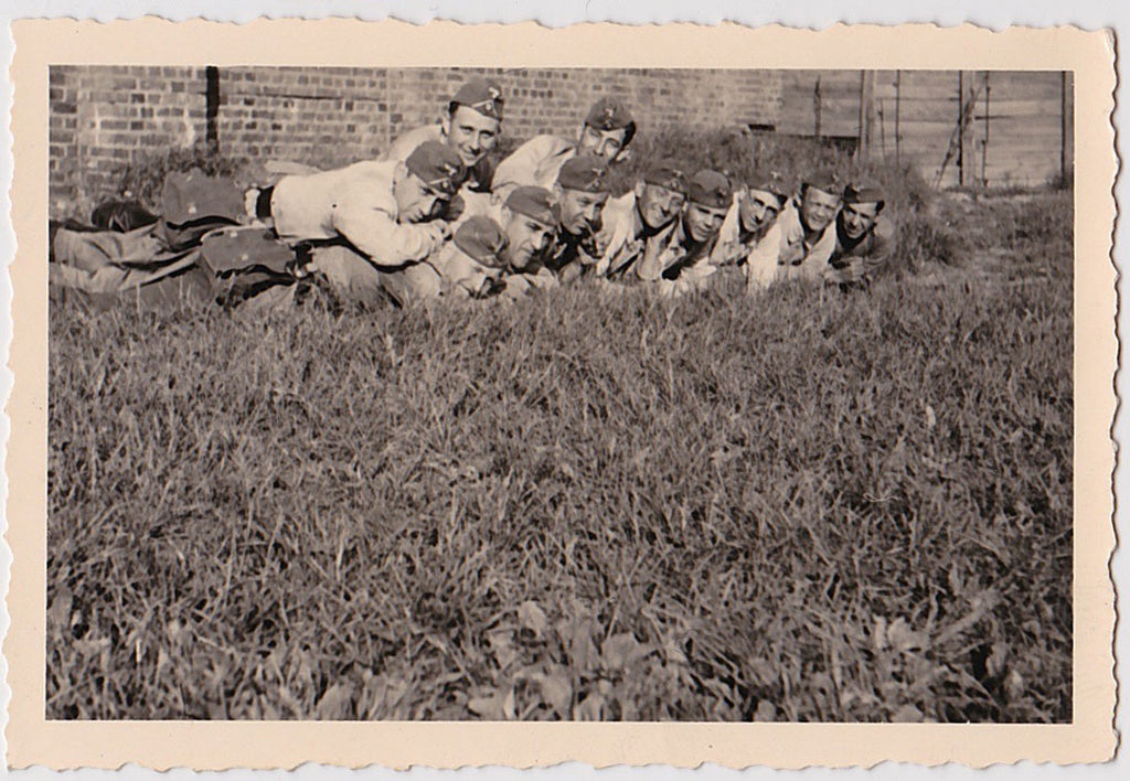 Men in row lying on top of one another.