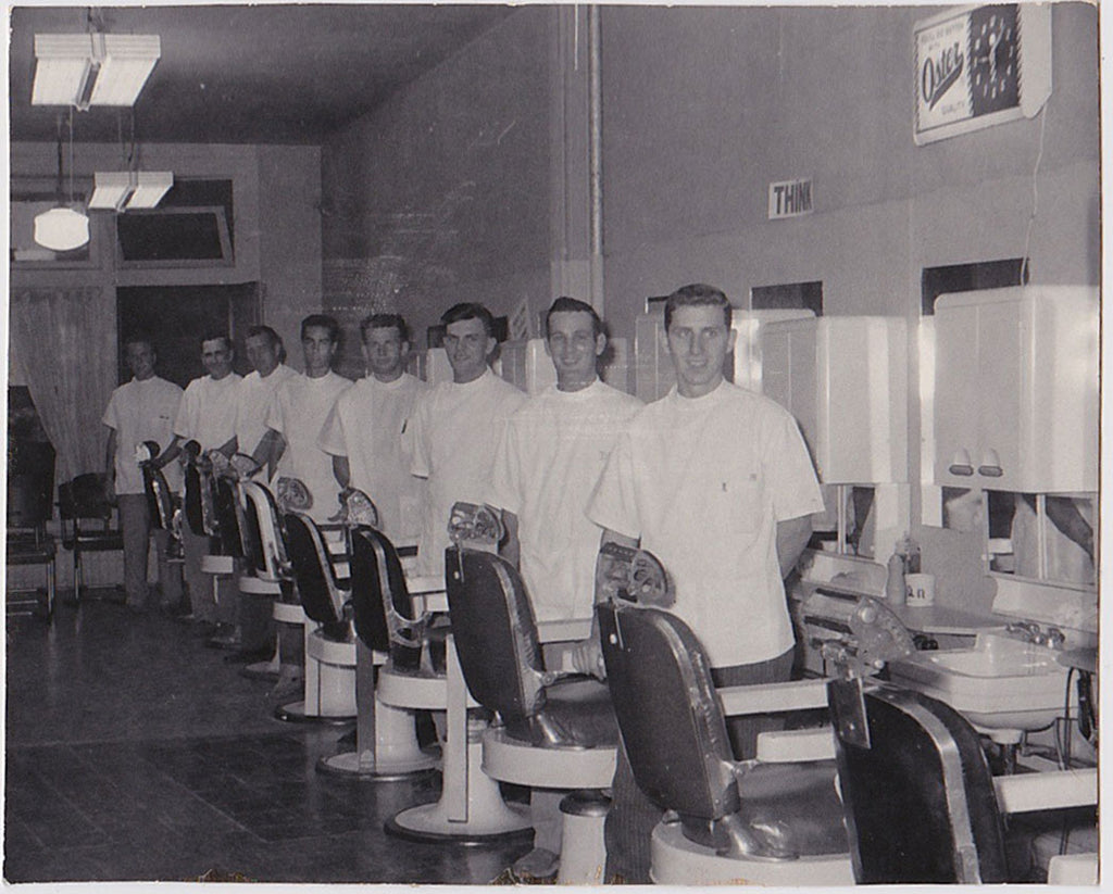 Vintage snapshot Eight young barbers stand by their chairs.