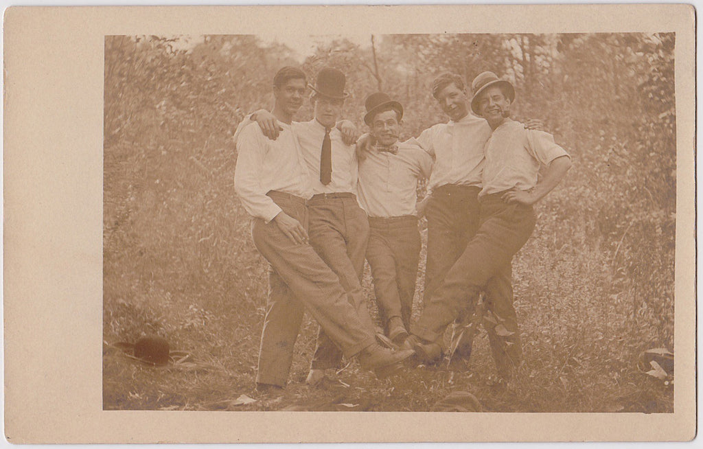 Vintage sepia Real Photo Postcard of five affectionate men sticking out one leg to join their feet in the middle.