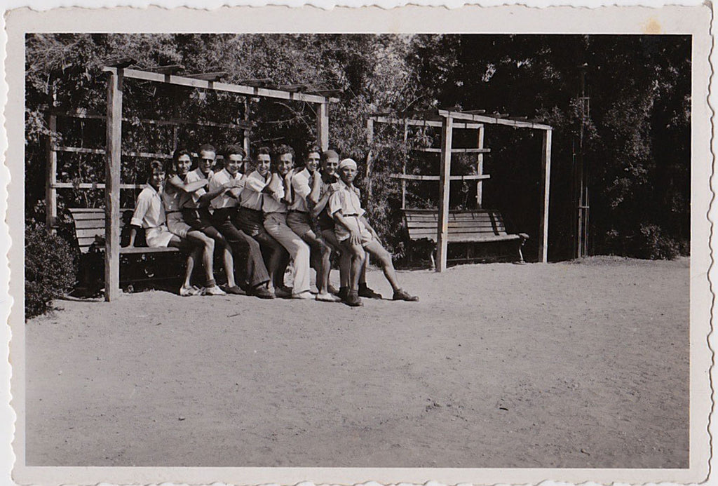 One man sitting on a bench with eight men on his lap, vintage snapshot 1950.