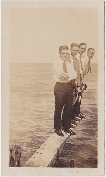 Four cute young guys wearing shirts and ties, carrying straw boaters, stand suspended over the water vintage photo