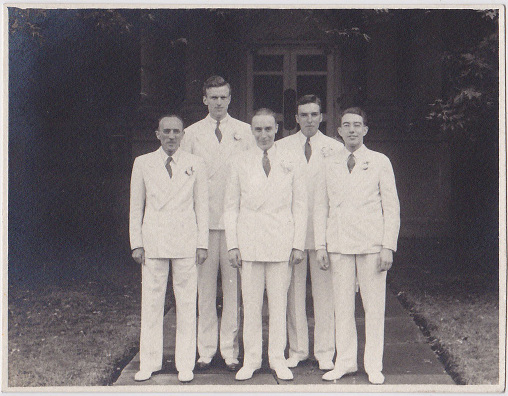 Five dapper gents in white suits with double-breasted jackets and a boutonniere, vintage snapshot