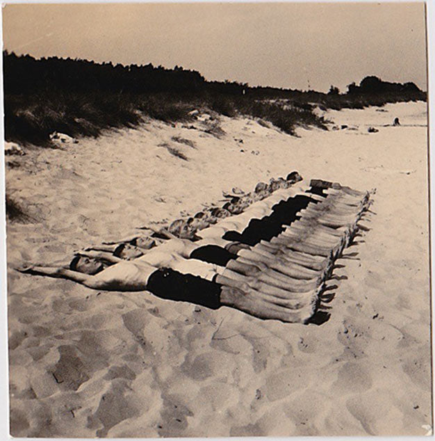 Amazing snapshot of a very long row of guys lying on the sand