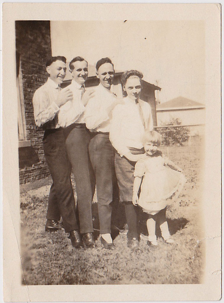 Charming vintage photo of four men posing with a little girl