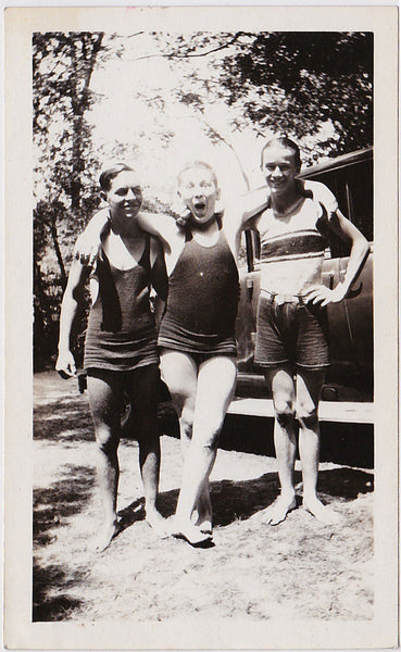 Three affectionate friends in swimsuits posing by their car