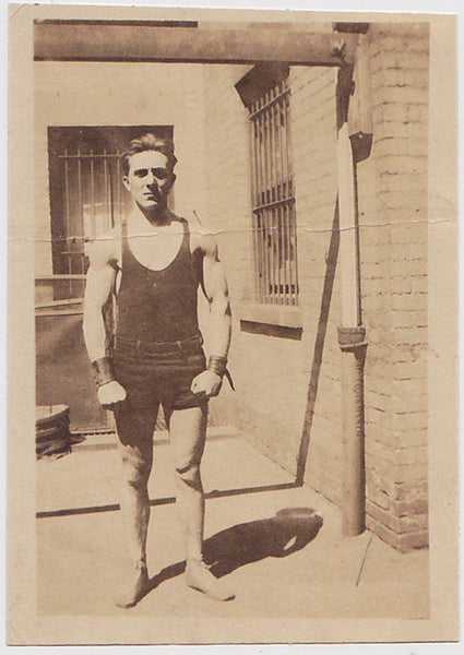 Bodybuilder wearing leather wristbands and a stern expression. vintage sepia photo