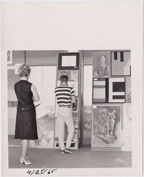 Young man looking at art. Older woman looking at young man, or so it seems.  Vintage photo 1965