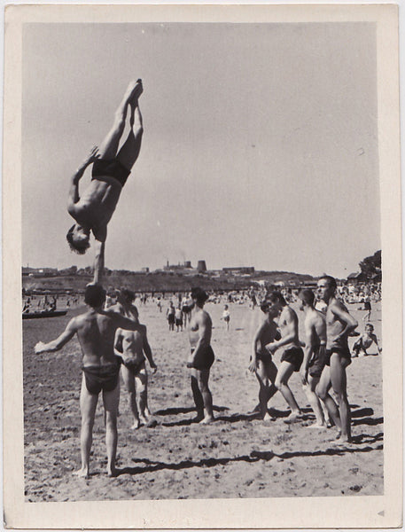A group of gymnasts have fun on the beach.    Vintage photo gloss finish, undated c. 1960s.