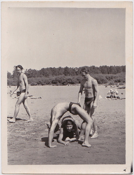 Three muscular gymnasts have fun on the beach  Vintage photo gloss finish, undated c. 1960s.