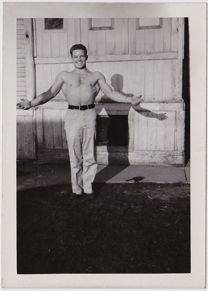 handsome, smiling bodybuilder flexing with his shirt off vintage photo