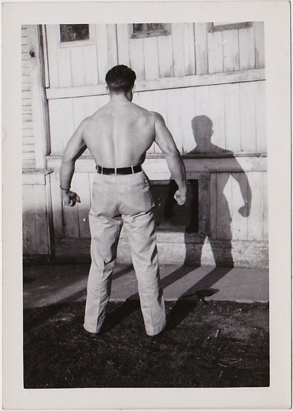 handsome bodybuilder flexing his massive back with his shirt off vintage photo