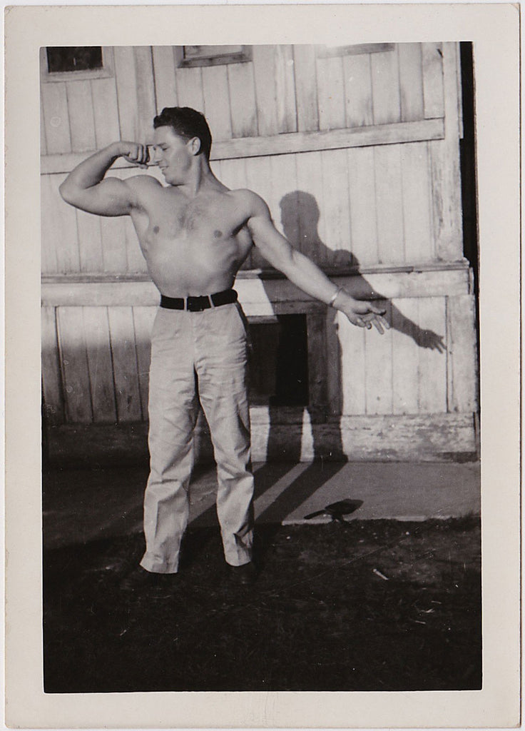 handsome, smiling bodybuilder flexing his bicep vintage photo