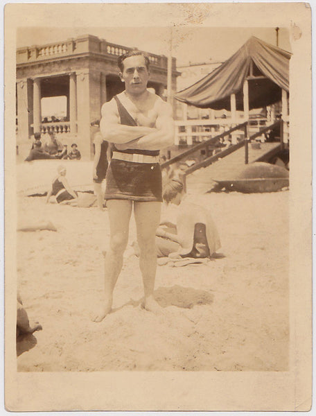 Undated vintage sepia photo of a bodybuilder on the beach in a tough guy pose.