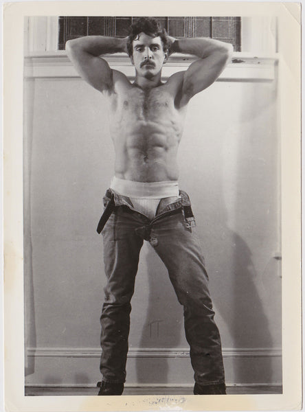 Vintage black and white photo of a handsome hairy stud flexing with his jeans lowered to reveal a jockstrap.