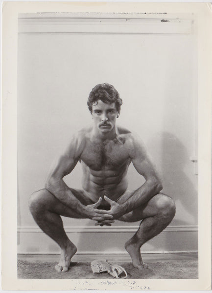 Vintage black and white photo of a handsome hairy stud Mario crouching over his jockstrap.