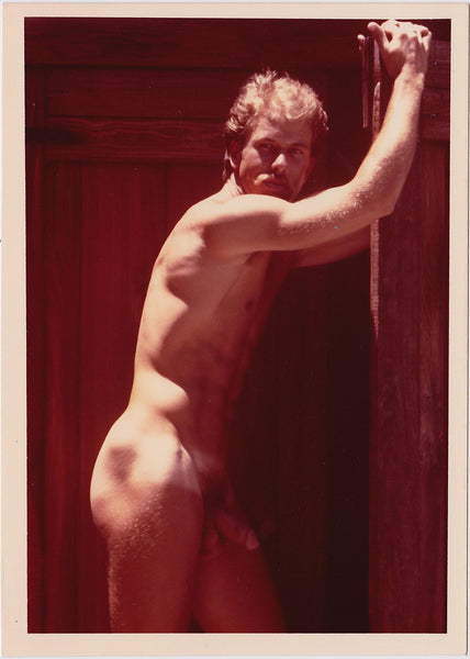 Vintage color photo of a handsome blond stud leaning on a wooden door, by Target Studio.