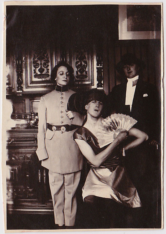 Rare and dramatic photos of what appears to be two women dressed as men and one man dressed as a woman.