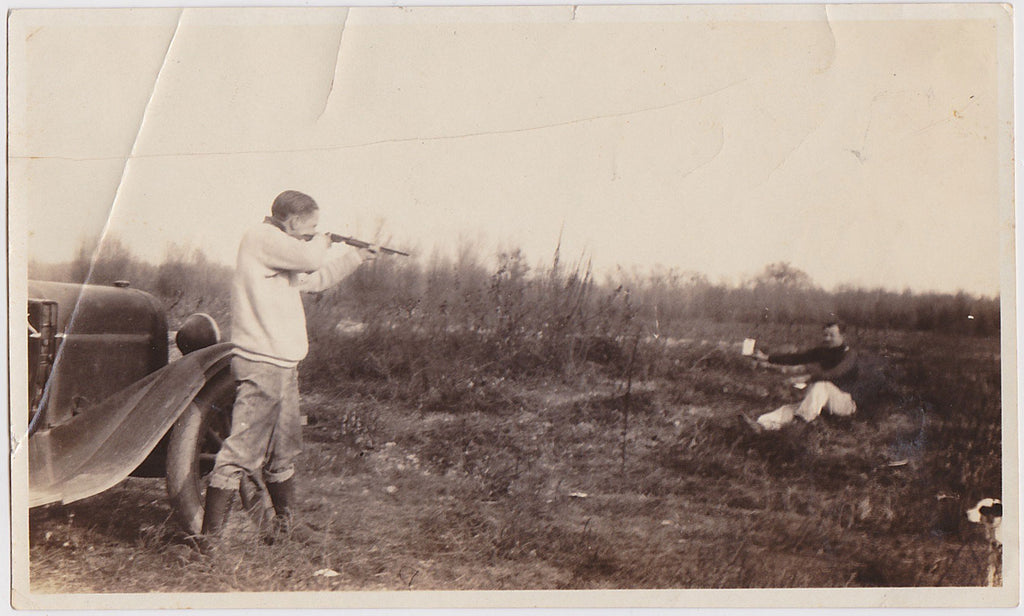 One person stands beside a car and aims a rifle at a small target held by another person vintage photo