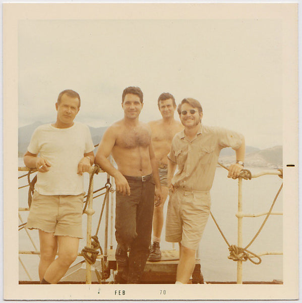 Four good-looking guys standing on a boat vintage color photo